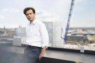 Germany, Berlin, portrait of businessman standing on roof terrace - FKF03130