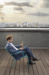 Germany, Berlin, businessman relaxing with drink on roof terrace at sunset looking at cell phone - FKF03133