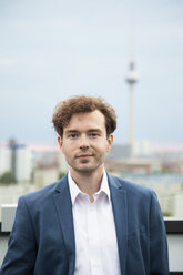 Germany, Berlin, portrait of  businessman with stubble and  curly brown hair on roof terrace - FKF03136