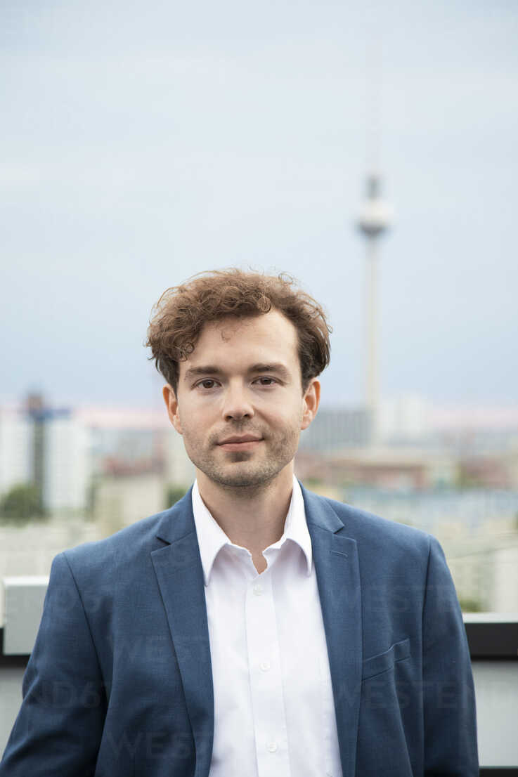 Germany, Berlin, portrait of  businessman with stubble and  curly brown hair on roof terrace - FKF03136 - Florian Küttler/Westend61