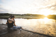 Female friends embracing while sitting on jetty over lake against sky during sunset - MASF09702