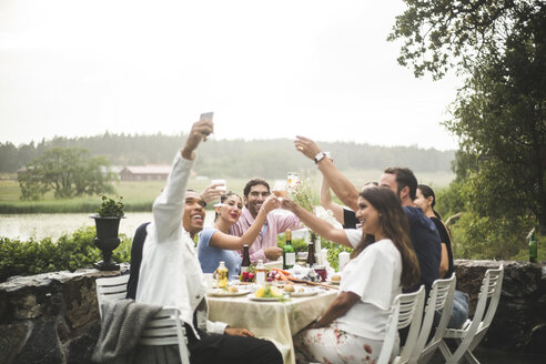 Smiling man taking selfie with friends holding drinks during dinner party in backyard - MASF09714