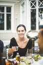 Portrait of smiling mid adult woman holding drink in glass while sitting at dining table against villa - MASF09717