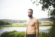 Portrait of confident shirtless man standing in backyard during weekend getaway - MASF09723