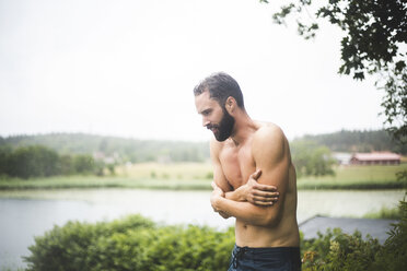 Shirtless mid adult man shivering while standing in backyard during weekend getaway - MASF09726