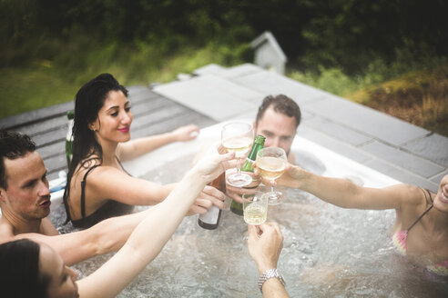 Carefree male and female friends toasting drinks in hot tub during weekend getaway - MASF09729