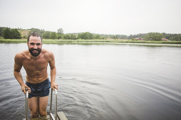 Portrait of smiling shirtless man standing on ladder at jetty over lake during weekend getaway - MASF09735