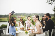 Cheerful young woman taking selfie with friends during dinner party in backyard - MASF09741