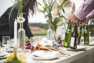 Cropped image of man holding beer bottles at dining table during dinner party in backyard - MASF09744