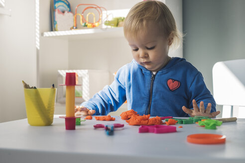 Portrait of baby girl playing with modeling clay - MOMF00546