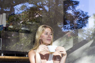 Portrait of woman in a cafe with cup of coffee looking out of window - LMJF00015