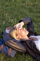 Woman lying on a meadow in a park relaxing - LMJF00030