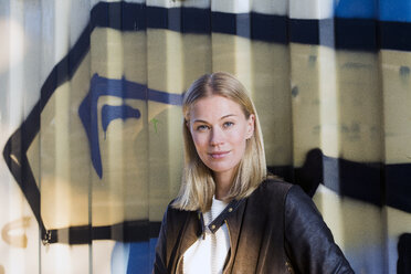 Portrait of blond woman in front of container - LMJF00033