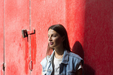Portrait of daydreaming young woman in front of red background - LMJF00036