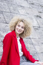 Portrait of smiling blond woman with ringlets wearing red coat - LMJF00051