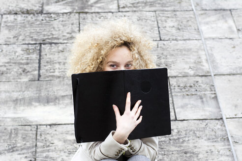 Blond woman with ringlets hiding behind black folder - LMJF00060