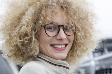 Portrait of smiling blond woman with ringlets wearing fashionable glasses - LMJF00063