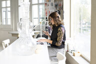 Young designer using smartphone in her atelier - AFVF02046