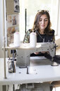 Portrait of young designer using sewing machine in her atelier - AFVF02055