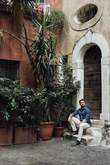 Businessman sitting on steps in a courtyard - BOYF01088