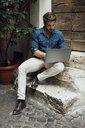Businessman sitting on steps in a courtyard using laptop - BOYF01091