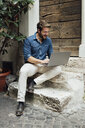 Laughing businessman sitting on steps in a courtyard using laptop - BOYF01100