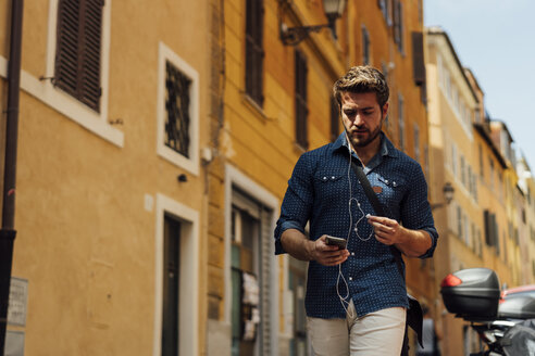 Businessman using earphones and cell phone outdoors - BOYF01109