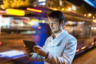 Portrait of smiling businessman looking at digital tablet on the street at night - DIGF05571