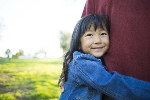 Cute little girl smiling while embracing father at park - TGBF01741