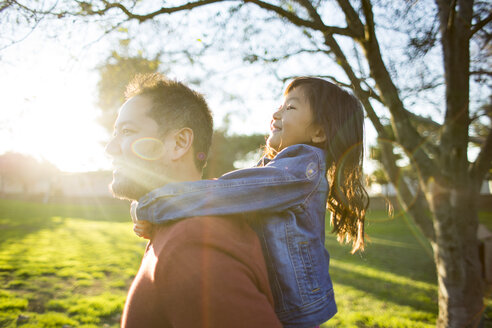 Side view of mature father piggybacking daughter at park - TGBF01744