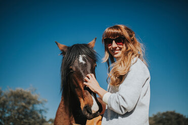 A young woman with a horse in the sun - INGF08139