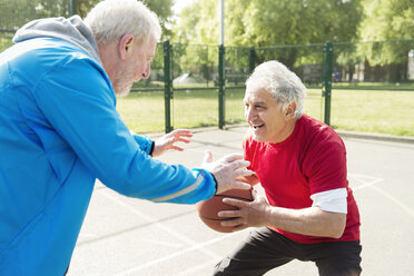 Active senior men friends playing basketball in sunny park - CAIF22269