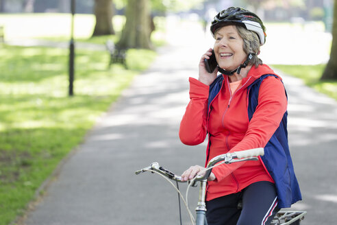 Active senior woman talking on cell phone on bike in park - CAIF22281
