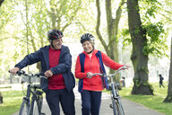 Active senior couple walking bikes in park - CAIF22287