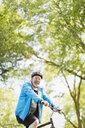 Portrait confident active senior man riding bike in park - CAIF22293