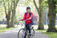 Portrait confident active senior woman riding bike in park - CAIF22296