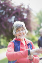 Portrait smiling, confident active senior woman checking smart watch in park - CAIF22299