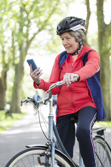 Active senior woman using smart phone on bike in park - CAIF22305