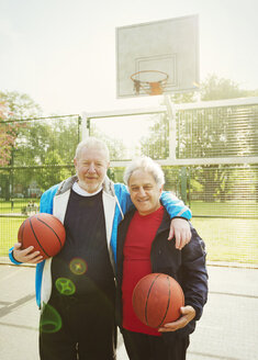 Portrait confident active senior men friends playing basketball in sunny park - CAIF22329