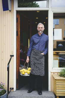 Portrait of confident salesman holding fruit basket while standing at store entrance - MASF09756