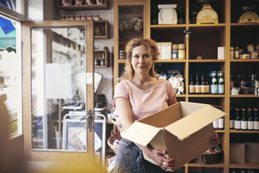 Portrait of confident saleswoman carrying cardboard box against rack in deli - MASF09774