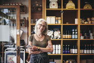Portrait of confident senior saleswoman standing against rack in deli - MASF09777