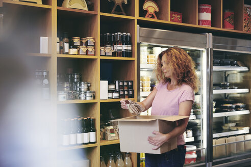 Saleswoman carrying box while working in deli - MASF09780