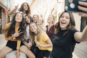Happy woman taking selfie with friends through smart phone at city - MASF09819