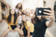 Young woman taking selfie with friends through smart phone at city - MASF09822