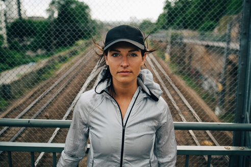 Portrait of confident female athlete standing against railing on bridge - MASF09906