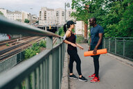 Sportsman holding yoga mat while talking with female athlete on footbridge in city - MASF09909
