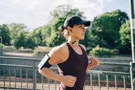 Confident sportswoman listening music while jogging on bridge in city - MASF09912