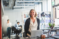 Happy creative businesswoman looking away while standing at desk in office - MASF10002