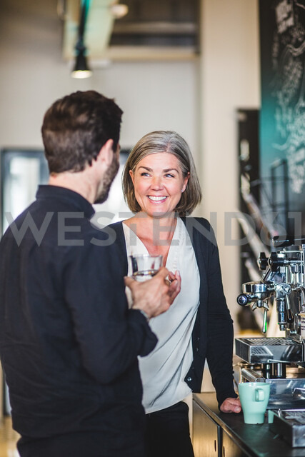 Business people talking while standing by coffee maker at office cafeteria - MASF10005 - Maskot/Westend61